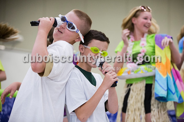 """Cedar Crest Intermediate School sixth-graders Reid Jochem, left, and Conner Tretter pretended to sing as their classmate Mya Englert danced during their class' performance set to the song """"Pool Party"""" by The Aquabats at the 11th annual lip sync show at the school in Bretzville on Wednesday. Each of the eight homeroom classes performed a song for students, staff and parents on the last day of school. Sarah Ann Jump/The Herald"""