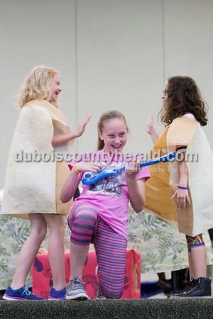 """Cedar Crest Intermediate School fifth-grader Macie Rickenbaugh played an inflatable guitar as her classmates Sophia Gentry, left, and Anna Hulsman, dressed as peanut butter and jelly, interacted during their class' performance set to the song """"Eat It"""" by """"Weird Al"""" Yankovic at the 11th annual lip sync show at the school in Bretzville on Wednesday. Sarah Ann Jump/The Herald"""