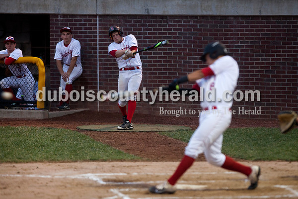 Tegan Johnston/The Herald Southridge's Jayce Harter practiced batting as Ross Eckert hit the ball during Thursday's Class 3A sectional championship at Ruxer Field in Jasper. Southridge defeated Washington 7-5.