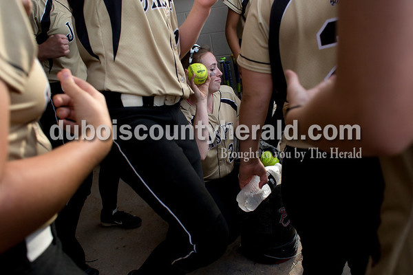 Wither her teammates dancing around her, Jasper's Molly Mehringer provided the rhythm by beating two softballs on a bucket during Monday's Class 3A softball sectional opener against Pike Central in Jasper. The Wildcats defeated Pike Central 3-0. Dave Weatherwax/The Herald