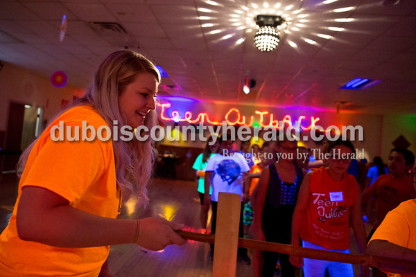 Sarah Ann Jump/The Herald Teen Outback director Allison Bounds of Huntingburg lowered the limbo pole during Friday's fiesta for third- through fifth-grade aged children at the youth center in Huntingburg.