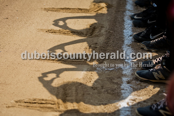 """Southridge players created heart-shaped shadows with their hands after writing the letter """"L"""" in the sand in memory of Lexi Mattingly as the team lined up for the national anthem during Saturday's 3A softball sectional championship game in Jasper. Vincennes Lincoln defeated Southridge 10-2. Sarah Ann Jump/The Herald"""