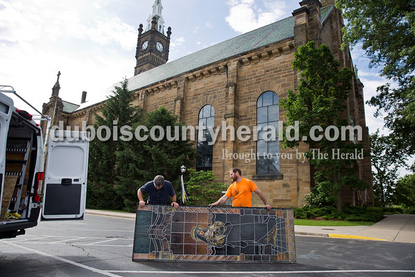 Sarah Ann Jump/The Herald Church maintenance supervisor Pat Gehlhausen of Jasper, left, and Conrad Schmitt Studios employee Brian Hummer of Waukesha, Wis. examined a stained glass window panel before loading it in the studio's van at St. Joseph Catholic Church in Jasper on Tuesday morning.