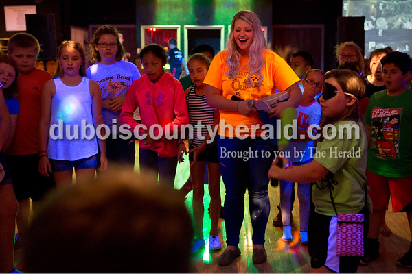 Sarah Ann Jump/The Herald Teen Outback director Allison Bounds of Huntingburg reacted as children swung at a piñata during Friday's fiesta for third- through fifth-grade aged children at the youth center in Huntingburg.