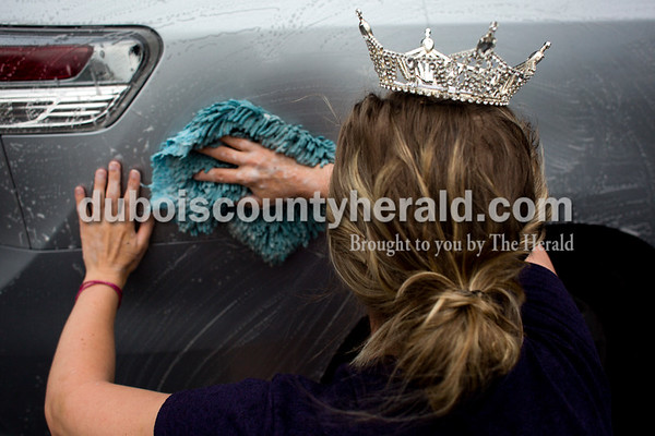 Tegan Johnston/The Herald Miss Northwest Territory Queen Charlotte Olson of Ireland, 24, wiped down a van during a fundraiser car wash on Saturday at the Hometown IGA in Jasper. All proceeds went towards the Children's Miracle Network and state fees.