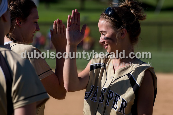 Jasper's Meredith Hilgefort, left, and Hailey Hurst exchanged a handshake while waiting for player introductions before Monday's Class 3A softball sectional opener against Pike Central in Jasper. The Wildcats defeated Pike Central 3-0. Dave Weatherwax/The Herald