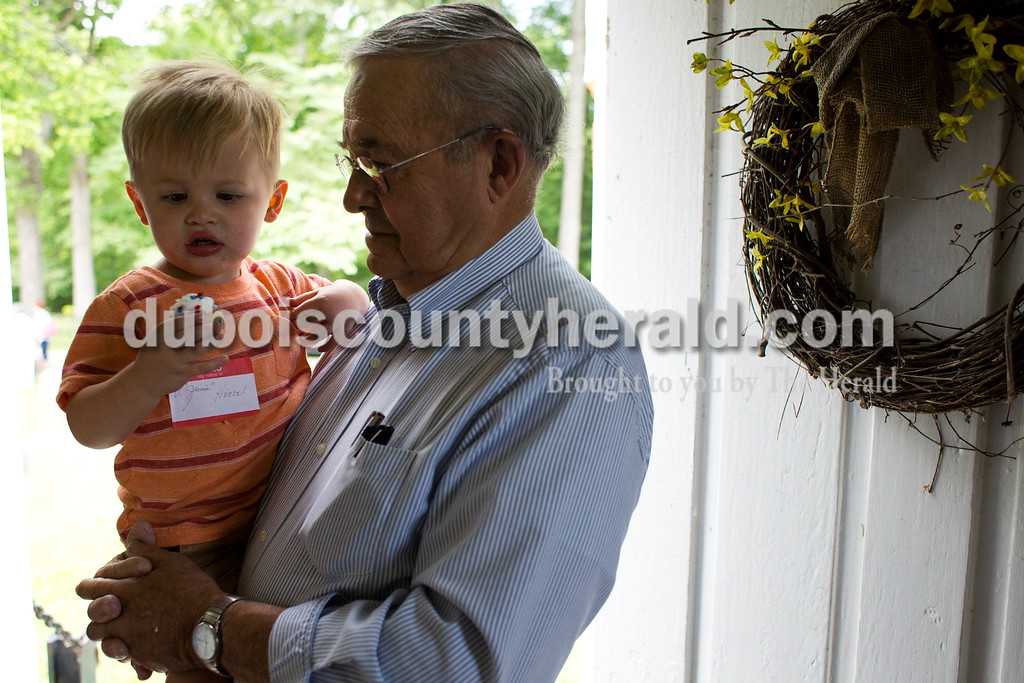 "Tegan Johnston/The Herald<br /> Delbert ""Junie"" Himself, of Ireland, held his two-year-old great-grandson Breccan Berg as he ate a cupcake during the Shiloh bicentennial celebration at Shiloh Meeting House in Ireland. Dozens gathered to enjoy vocal performances, a brief history on the historic site, desserts and more. Scotish-Irish pioneers built ""Old Shiloh,"" a small round log church, in 1817, but the present meeting house was build in 1849."