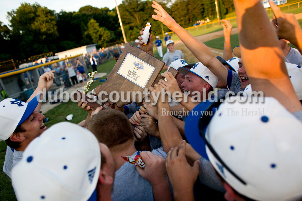 Tegan Johnston/The Herald<br /> Northeast Dubois' players huddled around the trophy in celebration after winning Monday's Class 1A sectional championship in Dubois. Northeast Dubois defeated Wood Memorial 5-1.