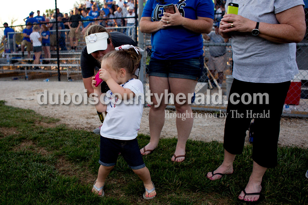 Tegan Johnston/The Herald<br /> Brynley Woolems of Dubois, 2, pretended to snap photos on her Barbie cellphone after Northeast Dubois boys baseball won Monday's Class 1A sectional championship in Dubois. Northeast Dubois defeated Wood Memorial 5-1.