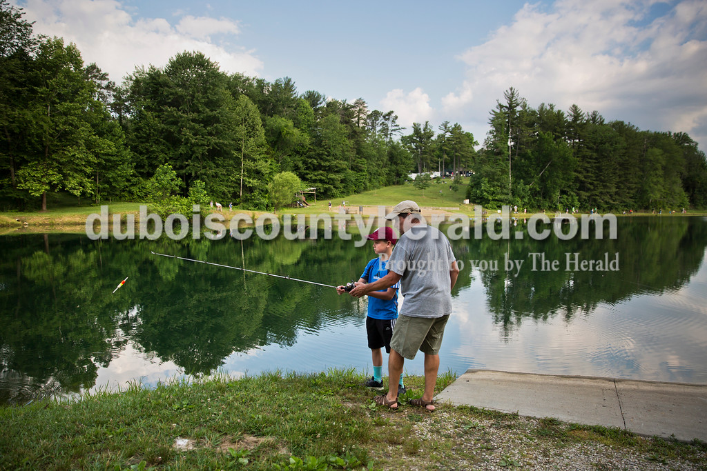 "John Welp of Jasper showed his 10-year-old son Levi proper casting technique during the fishing derby at the Jasper Outdoor Recreation on Saturday morning. The 7th annual fishing derby sponsored by the Dubois County Sportsmen's Club and the Huntingburg Conservation Club drew over 40 youth participants. ""We're trying to promote the outdoors to the kids. We want to introduce the sport of fishing and teach the ethical and moral way to do it,"" said John Toy of Jasper, a member of the Dubois County Sportsmen's Club who served as a judge. Sarah Ann Jump/The Herald"