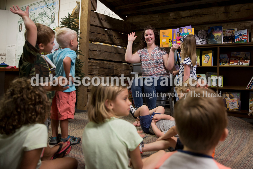 Amy Weyer of Ferdinand asked children to raise their hands if they could relate to the story as she read during story time at the Dubois County Museum in Jasper on Tuesday morning. Sarah Ann Jump/The Herald