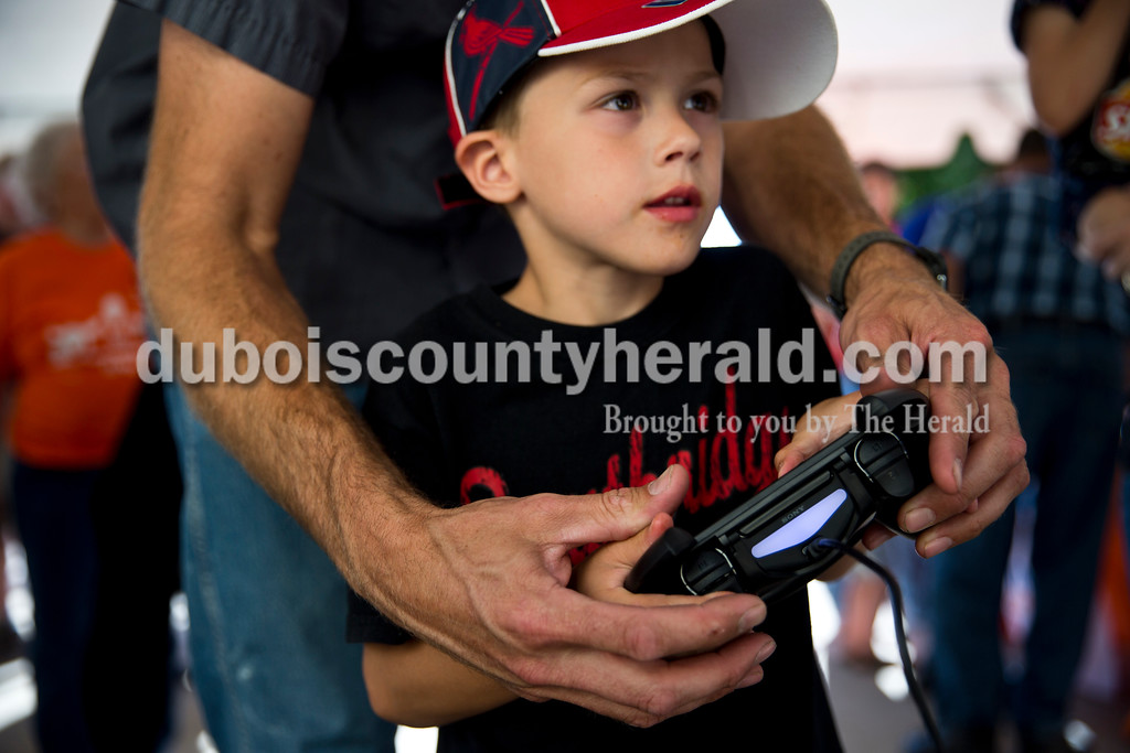 Sarah Ann Jump/The Herald<br /> Jackson Arehart of Holland, 6, played a race car video game with help from his father Andy during Joey Gase Day at Best Home Furnishings in Ferdinand Tuesday evening.