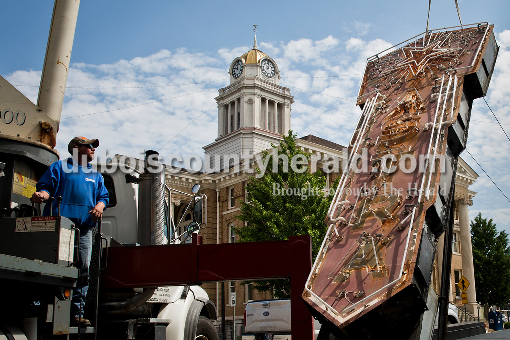 "Sarah Ann Jump/The Herald<br /> Custom Sign and Engineering Inc. employee Adrian Hilborn of Elberfeld controlled the crane lowering the Astra Theatre sign onto the truck bed outside of the theatre on Courthouse Square in Jasper on Monday. The sign is going to be cleaned, painted and refurbished. ""It's a really powerful, visual milestone we've achieved,"" said Selena Vonderheide of Jasper, a member of Next Act, Inc. ""It's the first step, that the public can see, of the restoration to come."""