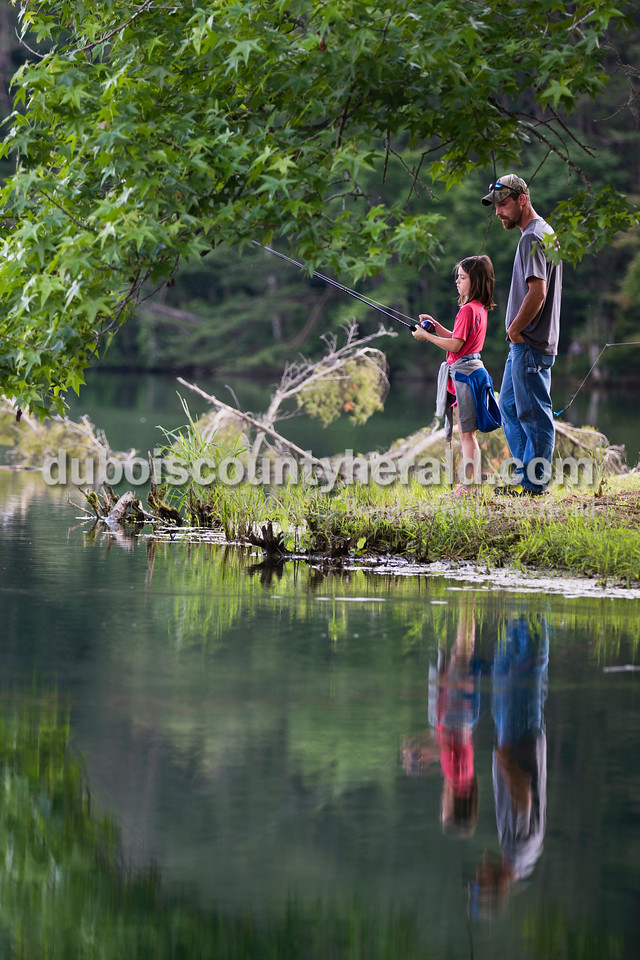 Sophia Denu of Birdseye, 10, fished under the watchful eye of her father Zach Denu during the fishing derby at the Jasper Outdoor Recreation on Saturday morning. Sarah Ann Jump/The Herald