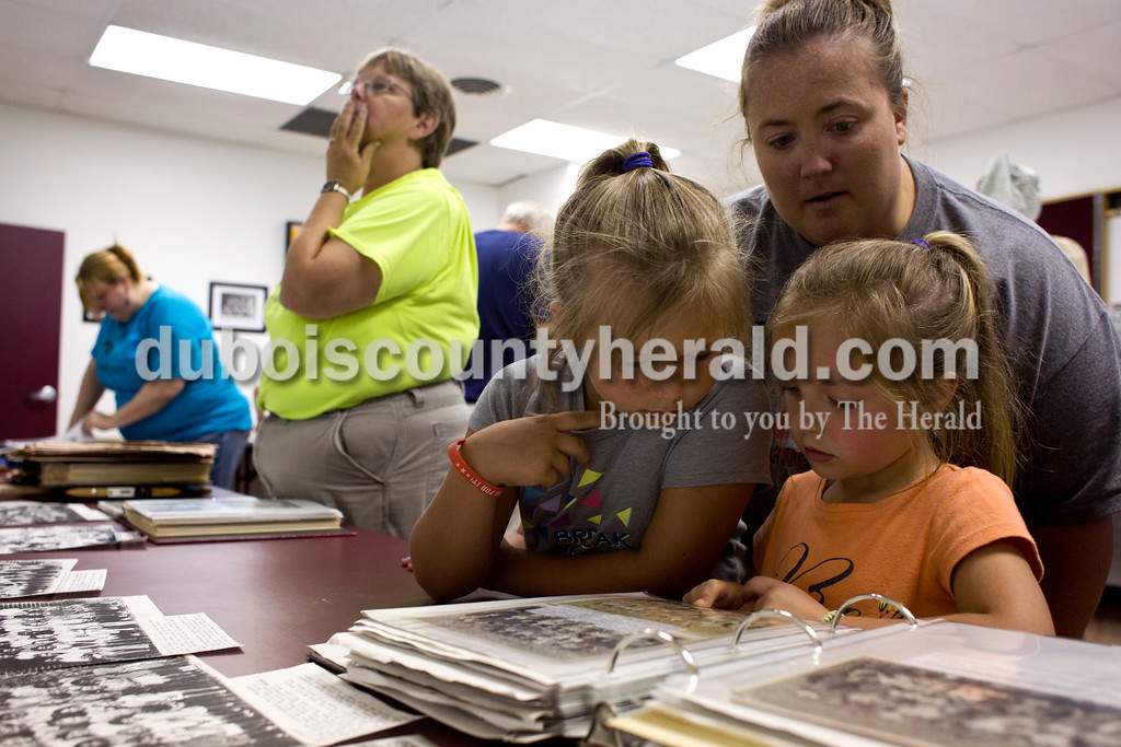 Tegan Johnston/The Herald<br /> Erica Rainey of Huntingburg and her daughters Addysen, 7, left, and Hadley, 5, looked through old photographs to find images of Erica's grandfather, Robert Weitkamp, who graduated with the class of '54 during the town of Stendal's 150 year celebration on Saturday. The two-day event offered family fun activities including a Tin Fest car show, an airplane flyover, a parade through town, musical performances, food and more. Stendal High School alumni also enjoyed a reunion and historical display during the town's festival.