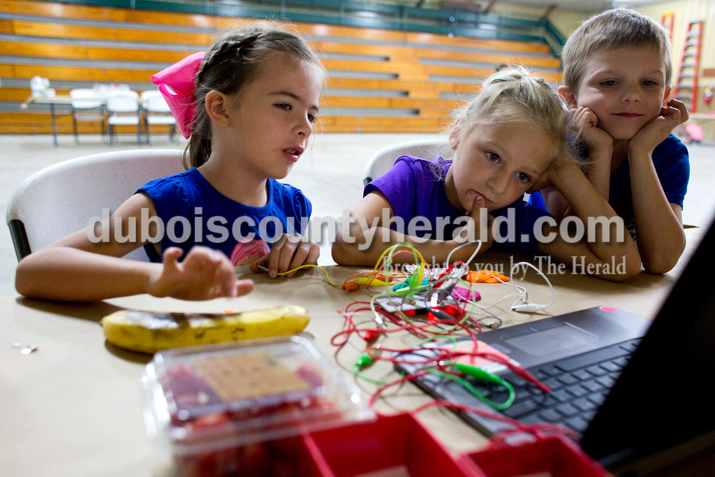 Tegan Johnston/The Herald<br /> Ellie Meunier of Ferdinand, 6, center, and Xavier Kiefer of Jasper, 6, watched as Mallory Morrison of Ferdinand, 6, tapped on a banana to play a game while learning about conducting electricity during Wednesday's Exploring 4-H Day Camp in the Clover Pavilion at the the Dubois County 4-H Fairgrounds in Bretzville. Purdue Extension hosted two days of Makers Mania: Experience a Day of Tinkering, Building, & Designing, a one-day camp that allowed children from kindergarten to second-grade to create and to experiment with different technology.