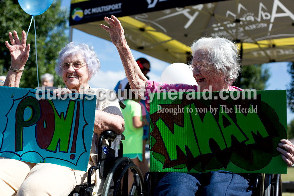 Tegan Johnston/The Herald<br /> St. Charles Health Campus residents Marian Caldemeyer, left, and Bernadette Grazier waved at attendees during the fifth annual Trilogy 200 Wellness Tour on Thursday at St. Charles Health Campus in Jasper. About 40 cyclists made a scheduled stop at the health campus to talk with residents and promote healthy living. The Trilogy 200 is a three-day, 200 mile wellness ride from Terre Haute to Tell City.