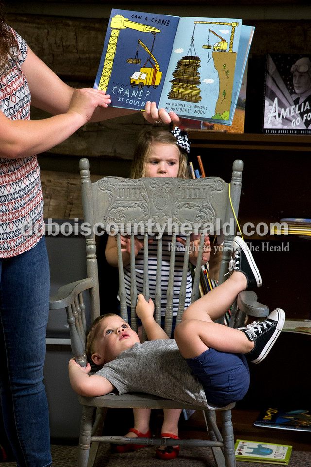 Henry Weyer of Ferdinand, 2, played on the rocking chair as his sister Hannah, 3, hid behind it while their mother Amy Weyer read a book during story time at the Dubois County Museum in Jasper on Tuesday morning. Sarah Ann Jump/The Herald