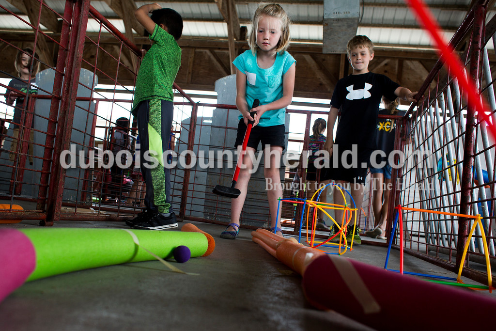 Tegan Johnston/The Herald<br /> Camille Betz of Celestine, 6, putted her ball down the mini golf course she designed with Ricardo Vanegas of Huntingburg, 6, during Wednesday's Exploring 4-H Day Camp in the Clover Pavilion at the the Dubois County 4-H Fairgrounds in Bretzville. Purdue Extension hosted two days of Makers Mania: Experience a Day of Tinkering, Building, & Designing, a one-day camp that allowed children from kindergarten to second-grade to create and to experiment with different technology.