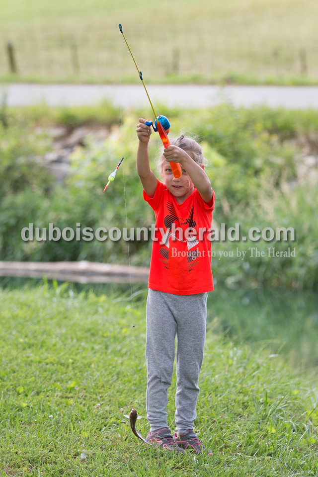 Quinn Weidenbenner of Jasper, 6, held up her catch to show her father Phil Barth during the fishing derby at the Jasper Outdoor Recreation on Saturday morning. Sarah Ann Jump/The Herald