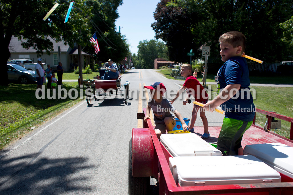 Tegan Johnston/The Herald<br /> Lucas Reller, 6, right, his brother Conner, 5, center, and Bryer Tincher, 8, all of Stendal, threw ice pops during the parade at the town of Stendal's 150 year celebration on Saturday. The two-day event offered family fun activities including a Tin Fest car show, an airplane flyover, a parade through town, musical performances, food and more. Stendal High School alumni also enjoyed a reunion and historical display during the town's festival.