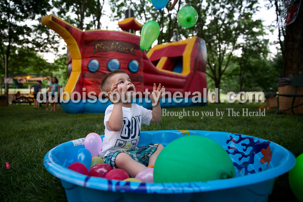 Calvin Mehringer of Jasper, 2, reached to catch balloons as his father Brent dropped them overhead during the Sisters' Summer Social at Monastery Immaculate Conception in Ferdinand on Friday. Sarah Ann Jump/The Herald