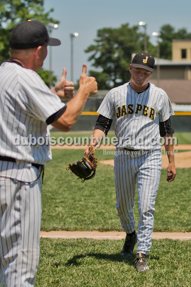 Jasper head coach Terry Gobert gave two thumbs-up to pitcher Reece Kleinhelter as he walked off the field at the end of the seventh inning during Saturday's Class 3A baseball semistate game at Ruxer Field in Jasper. Jasper defeated Northview 3-2 in 10 innings. Sarah Ann Jump/The Herald