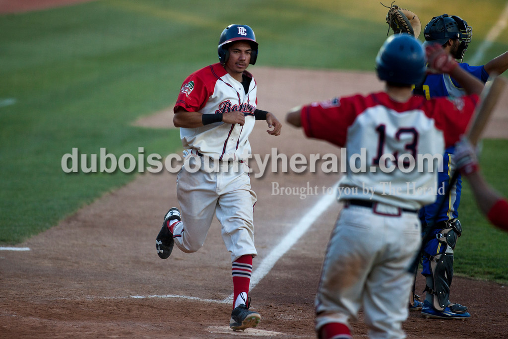 Tegan Johnston/The Herald<br /> Dubois County Bombers' Roman Trujillo ran into home plate scoring a second run from Craig Shepherd's hit during Thursday night's game at League stadium in Huntingburg. Dubois County defeated Henderson 6-1.