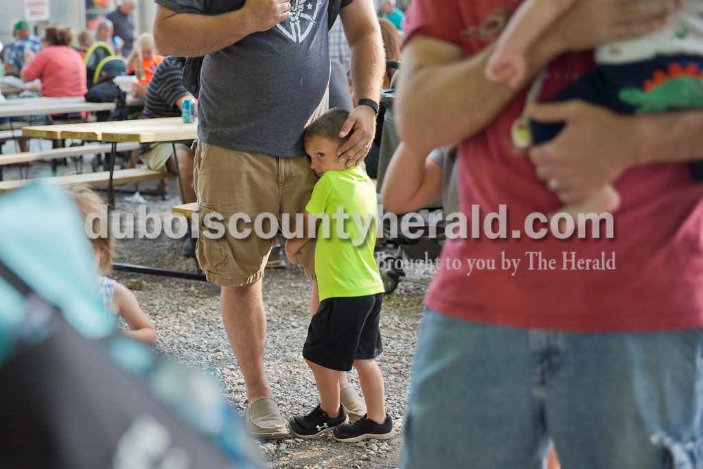 Sarah Ann Jump/The Herald<br /> Hudson Bauer of Jasper, 3, clung to his father Kirk's leg as they waited in line for twisted balloons during St. Henry Heinrichsdorf Fest on Friday evening. The town gathered for chicken dinners, children's games, music and a beer garden during the two day event.