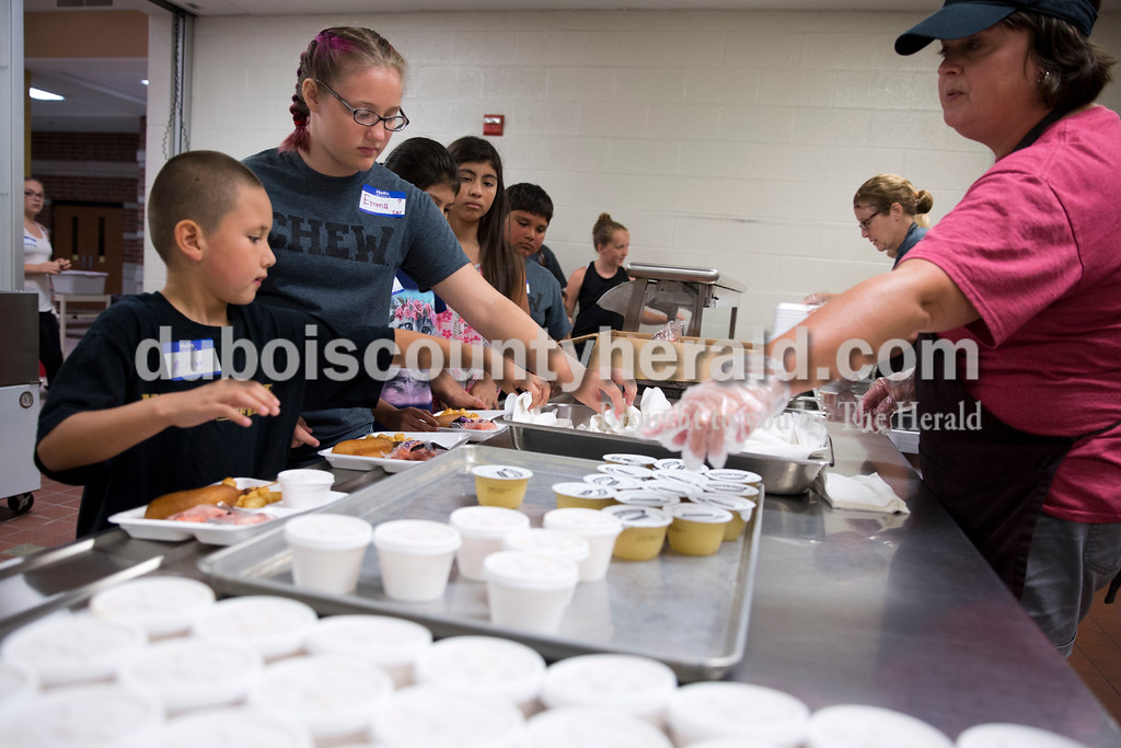 Sarah Ann Jump/The Herald<br /> Michael Kane of Jasper, 7, left, and Emma Garland of Huntingburg, 13, received a corn dog, tater tots, carrots and fruit for lunch during Community CHEW at Jasper Middle School on Thursday afternoon.