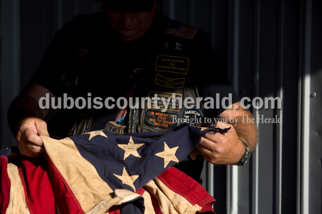 Tegan Johnston/The Herald<br /> Greg Smith with the American Legion Riders Post 147 in Jasper carefully looked at an old, faded flag waiting to be disposed of during Friday night's flag burning ceremony at the Dubois County 4-H Fairgrounds in Bretzville. The Dubois County Veterans Council hosted the ceremony where over 2,000 worn and tattered flags were disposed and where new flags could also be purchased.