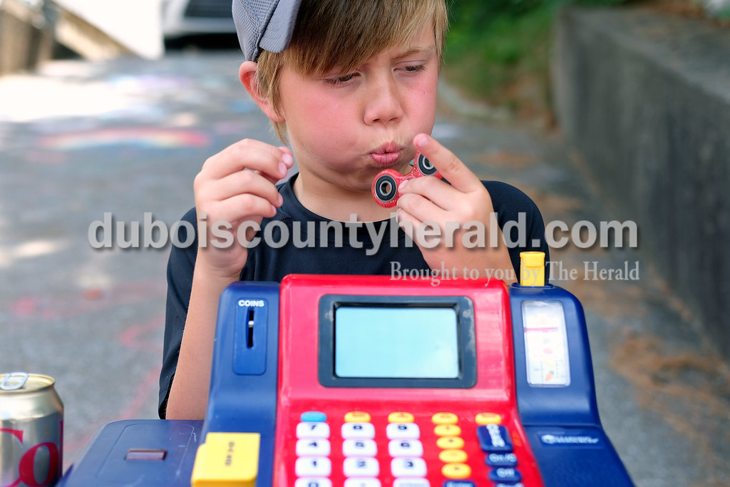 Dylan Durcholz of Jasper, 9, played with a fidget spinner while waiting for customers Monday.