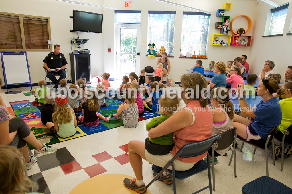 Sarah Ann Jump/The Herald<br /> Police Chief Lloyd Froman read three police-themed books to children during story time with Ferdinand Police officers at the Ferdinand Public Library on Tuesday morning.