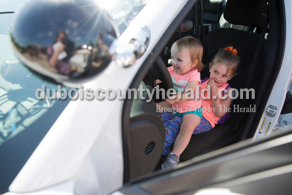 Sarah Ann Jump/The Herald<br /> Vera Heeke of Ferdinand, 1, pretended to steer while sitting on her three-year-old sister Ella's lap inside a Ferdinand Police patrol car after story time with Ferdinand Police officers at the Ferdinand Public Library on Tuesday morning. Police Chief Lloyd Froman read three police-themed books to the children. Afterwards, officer Eric Hopkins allowed them to explore the patrol vehicle.