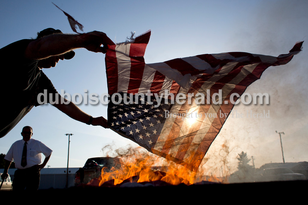 Tegan Johnston/The Herald<br /> Greg Smith with the American Legion Riders Post 147 in Jasper laid a torn flag over the fire during Friday night's flag burning ceremony at the Dubois County 4-H Fairgrounds in Bretzville. The Dubois County Veterans Council hosted the ceremony where over 2,000 worn and tattered flags were disposed and where new flags could also be purchased.