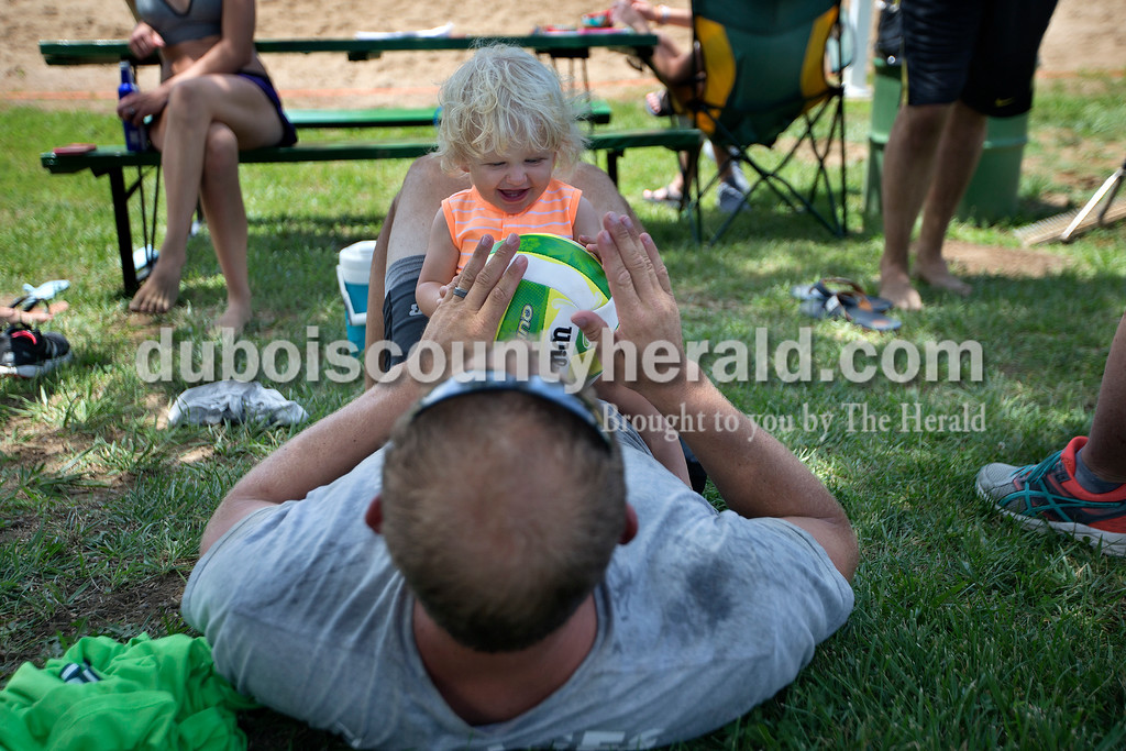 Brittney Lohmiller /The Herald <br /> Sway Voges, 14 months, played with his dad Blake Voges, both of Dale, in between co-ed volleyball matches during Heimatfest at 18th Street Park Saturday afternoon.