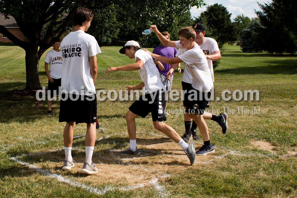 Tegan Johnston/The Herald<br /> Jasper's Josh Weidenbenner was congratulated by his teammates after scoring a home run while playing whiffle ball with his teammates on Tuesday afternoon at the Egbert's home in Ireland. Several of the players -- the original Ireland spuds -- have been playing whiffle ball at the Egbert's backyard diamond for about 14 years. The Jasper baseball team has created a tradition of playing whiffle ball together during tournament week. The Egbert family said they enjoy creating ways for the players to bond with each other in a more relaxed setting. Their son, Tanner, is a senior on the team, but the family said that the tradition is welcome to continue.
