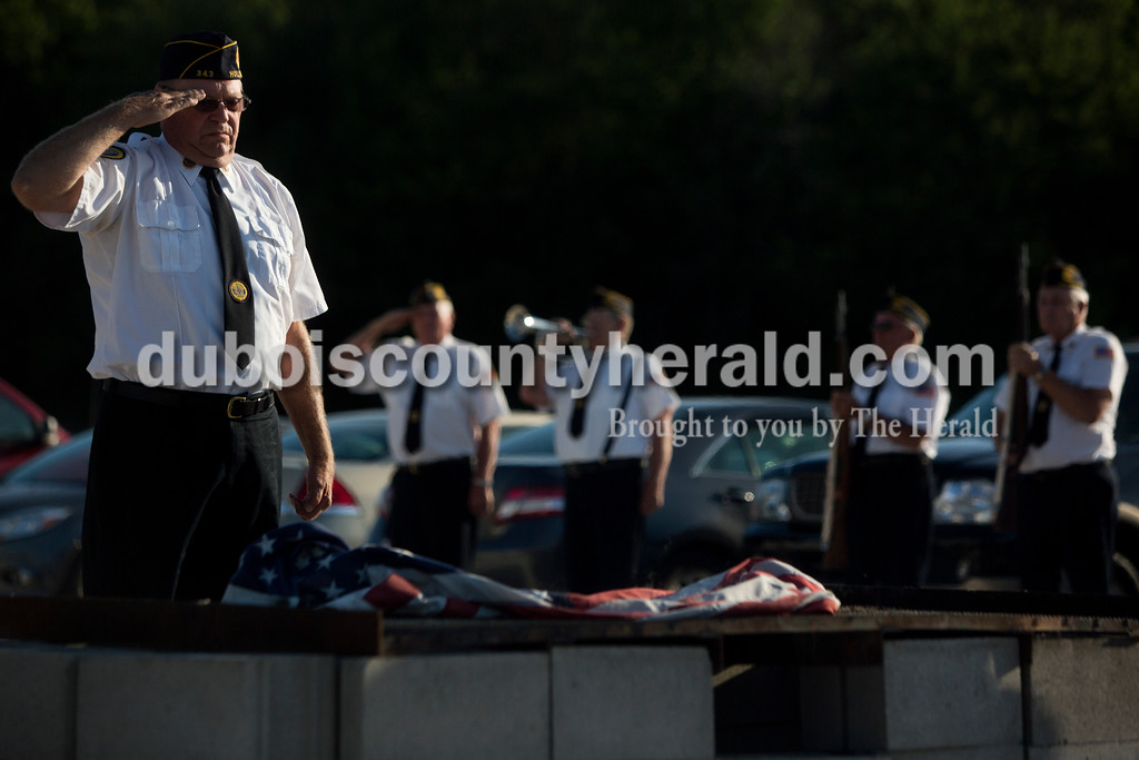 Tegan Johnston/The Herald<br /> Sergeant at Arms officer Bob Hunter with American Legions Post 343 in Holland saluted the flag during Friday night's flag burning ceremony at the Dubois County 4-H Fairgrounds in Bretzville. The Dubois County Veterans Council hosted the ceremony where over 2,000 worn and tattered flags were disposed and where new flags could also be purchased.