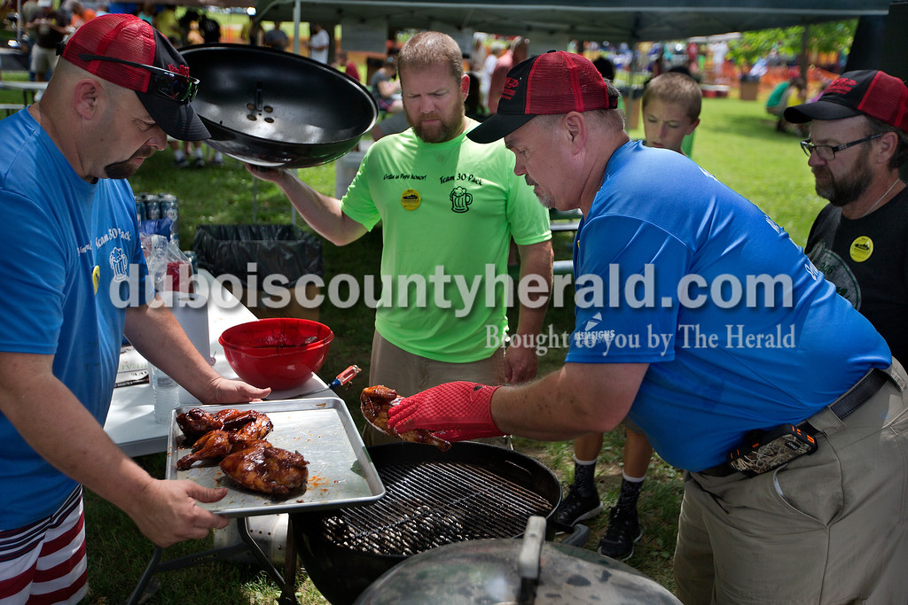 """Brittney Lohmiller /The Herald <br /> Mike Mullens of Saint Anthony, left, held out a tray as Terry Ebert of Saint Anthony moved chicken off of the grill while Eric Klem, his son Brody Klem, 13, both of Ferdinand and Doug Brosmer of Breztville watched while competing in the Backyard Barbecue contest during Heimatfest at 18th Street Park Saturday afternoon. """"It tastes like candy,"""" Mullens said as he tried a piece of chicken."""