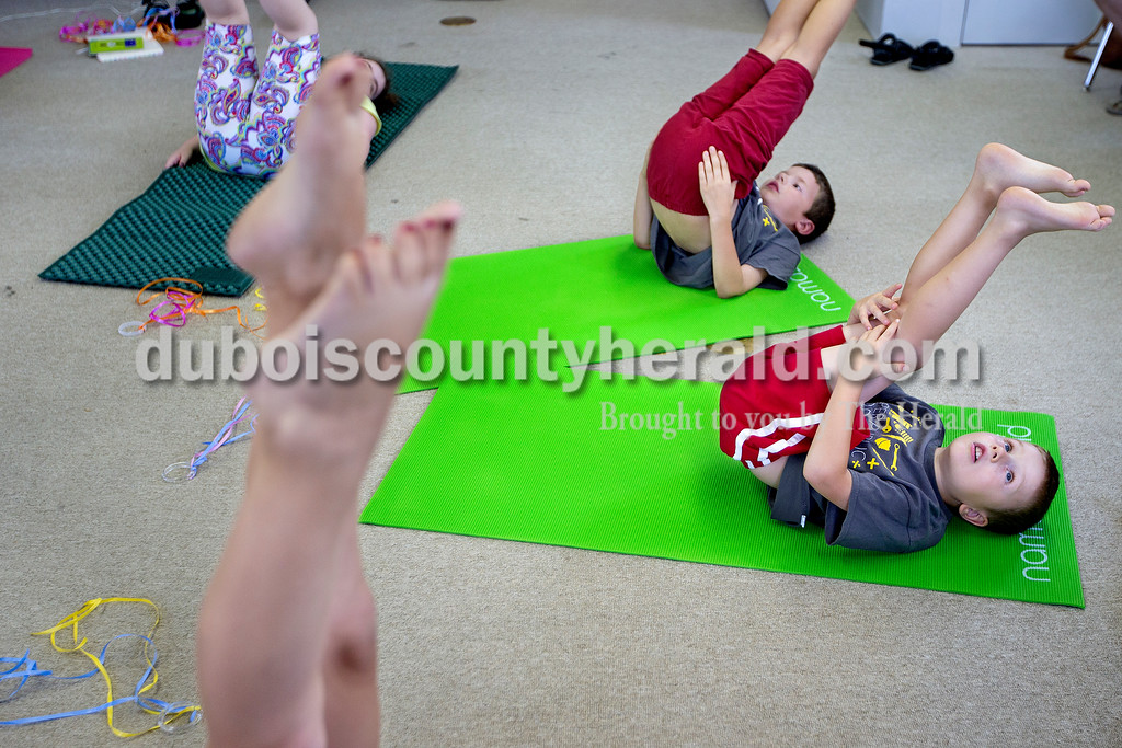 Brittney Lohmiller/The Herald <br /> From left: Kaitlyn Meyer of Dubois, 8, Martin Cooper of Jasper, 8, and Francis Cooper of Jasper, 6, practiced the candlestick yoga pose at the Jasper Public Library Annex Wednesday afternoon. Registered yoga instructor with Fire Horse Yoga Studio Amanda Gamble, who taught the hour long class, started practicing yoga while in graduate school to help with stress.