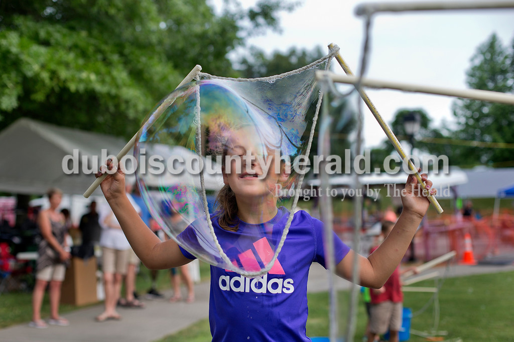 Brittney Lohmiller /The Herald <br /> Hattie Dilger of Ferdinand, 10, pushed her face into a large bubble during Heimatfest at 18th Street Park Friday evening.