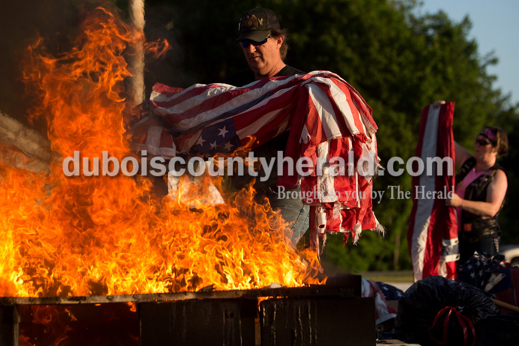Tegan Johnston/The Herald<br /> Greg Smith with the American Legion Riders Post 147 in Jasper carried multiple flags to be laid over the fire during Friday night's flag burning ceremony at the Dubois County 4-H Fairgrounds in Bretzville. The Dubois County Veterans Council hosted the ceremony where over 2,000 worn and tattered flags were disposed and where new flags could also be purchased.