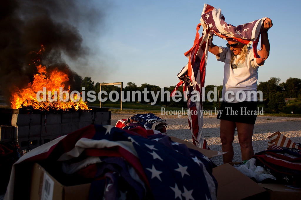 Tegan Johnston/The Herald<br /> Connie Brewster of Ferdinand pulled out old, torn flags needing to be disposed of during Friday night's flag burning ceremony at the Dubois County 4-H Fairgrounds in Bretzville. The Dubois County Veterans Council hosted the ceremony where over 2,000 worn and tattered flags were disposed and where new flags could also be purchased.