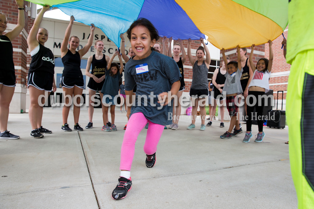 Sarah Ann Jump/The Herald<br /> Sophia Rankin of Jasper, 5, ran under a parachute as her peers and members of the Jasper High School dance team raised it during Community CHEW at Jasper Middle School on Thursday afternoon. Community CHEW (Child Hunger Ending Workshop) is a nonprofit organization that offers a hot meal and afternoon of activities to food insecure students in the Greater Jasper Schools and Holy Trinity Catholic School. On July 6, Community CHEW is inviting U.S. service members both present and past to come to the CHEW event so the students who participate in the program can learn about the importance of serving others by serving the service members lunch. They are asking service members to arrive at Noon at the middle school through Door 1.