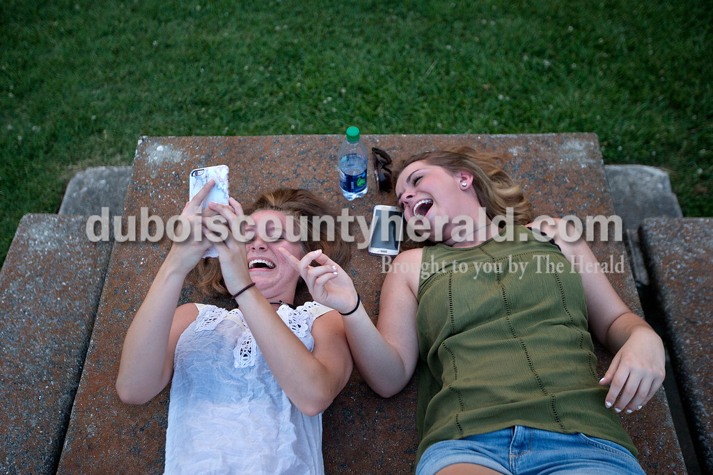 """Brittney Lohmiller /The Herald <br /> Thea Petry, left, of Saint Anthony, 14, and Meghan Dale of Ferdinand, 15, laughed while they looked through photos on Petry's phone during Heimatfest at 18th Street Park Friday evening. """"There's this app that we're kind of obsessed with and the photos on it made us laugh,"""" Petry said."""