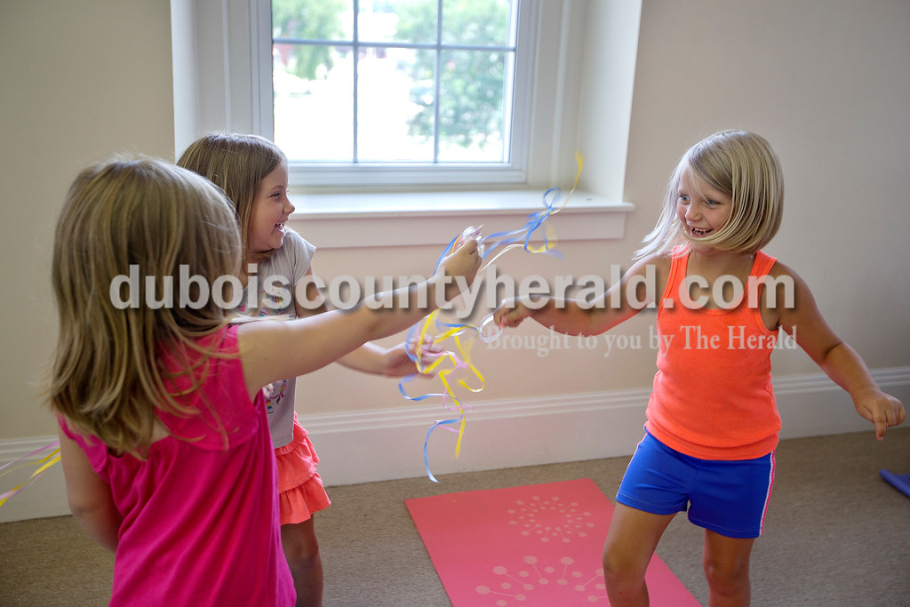 Brittney Lohmiller/The Herald <br /> From left: Ryla Czerwinski, 8, Haddie Hollingsworth, 6, and Jacey Booker, 7, all of Jasper, played with ribbons during a yoga for kids class offered at the Jasper Public Library Annex Wednesday afternoon. This was the first time a yoga class for kids was offered through the library. Registered yoga instructor with Fire Horse Yoga Studio, Amanda Gamble, is hoping to offer more classes in the fall.