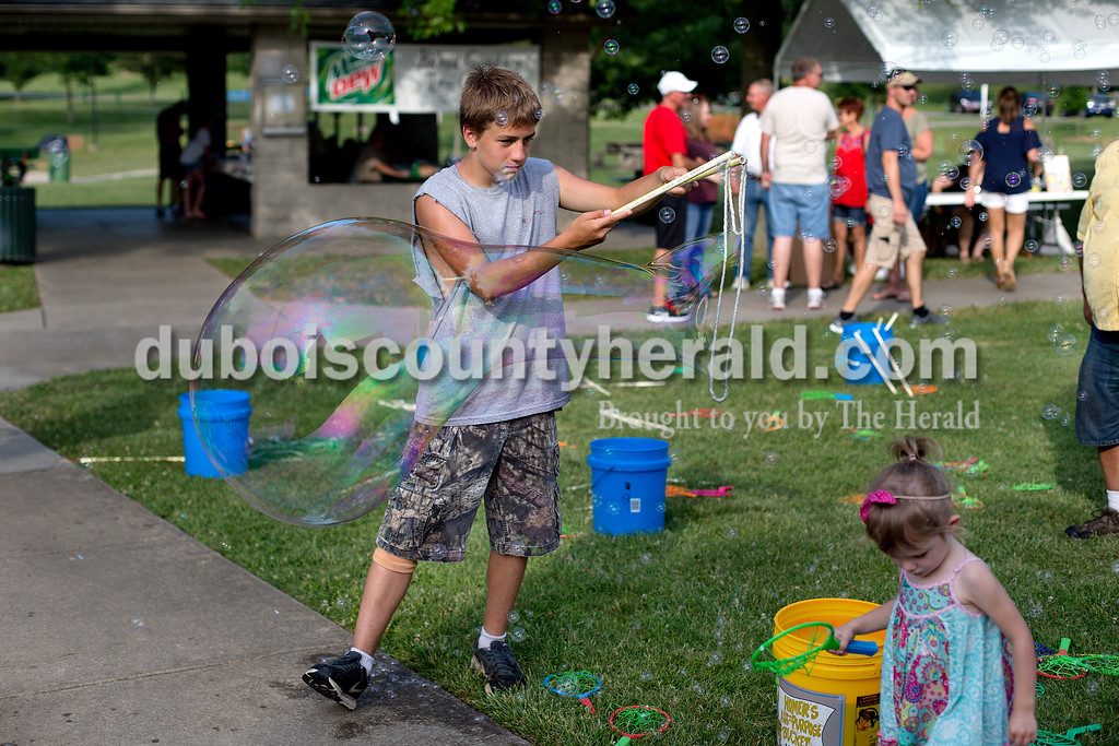Brittney Lohmiller /The Herald <br /> Issac Fuhrman of Ferdinand, 14, worked with a loop of yarn and soapy water to create a large bubble during Heimatfest at 18th Street Park Friday evening.