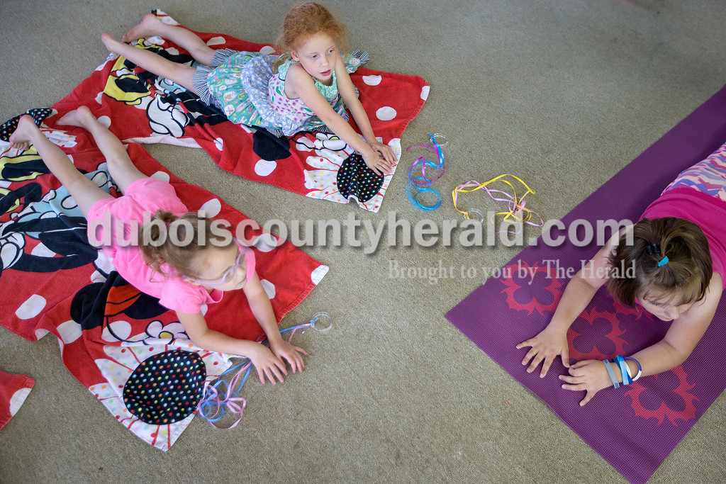 Brittney Lohmiller/The Herald <br /> From left: Josie Wiggins, 6, her sister Ella Wiggins, 6, and Lilly Hanshaw, 8, all of Jasper, practiced the cobra yoga pose at the Jasper Public Library Annex Wednesday afternoon. The 13 children who took the class learned a variety of poses that exercised different muscle groups from registered yoga instructor Amanda Gamble.