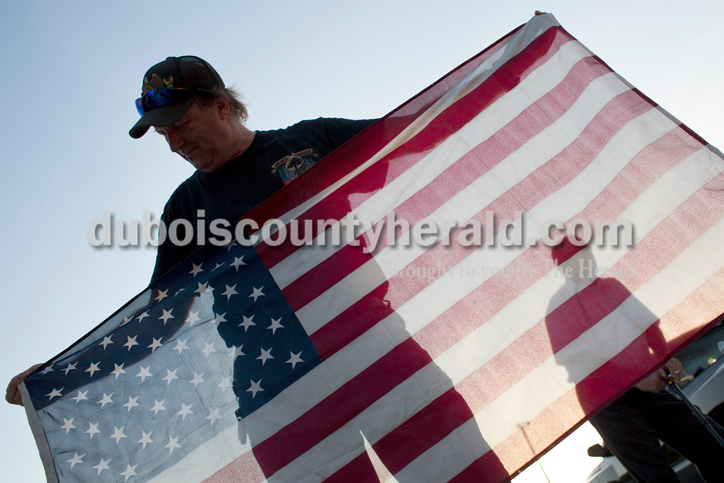 Tegan Johnston/The Herald<br /> Greg Smith with the American Legion Riders Post 147 in Jasper examined a faded flag before disposing of it during Friday night's flag burning ceremony at the Dubois County 4-H Fairgrounds in Bretzville. The Dubois County Veterans Council hosted the ceremony where over 2,000 worn and tattered flags were disposed and where new flags could also be purchased.