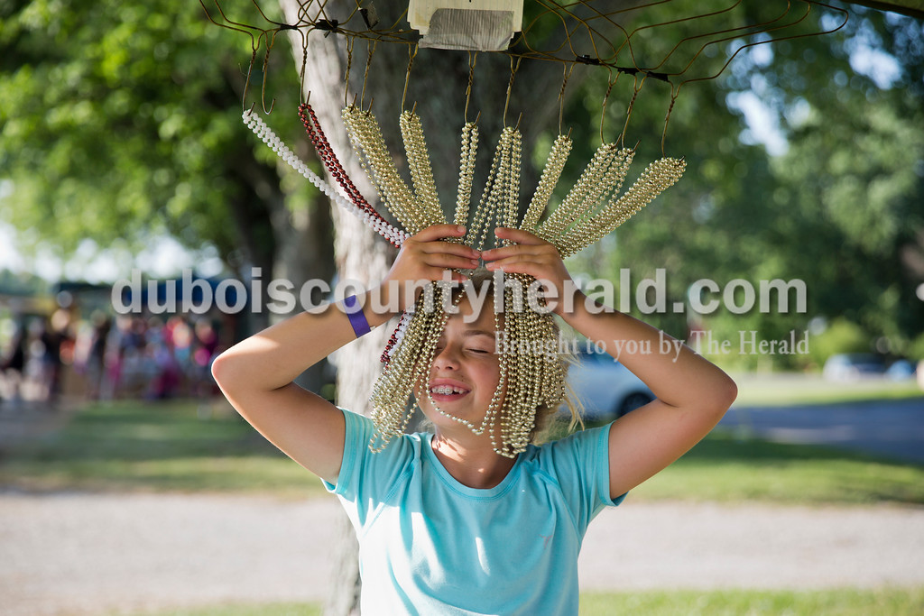Sarah Ann Jump/The Herald<br /> Mykela Tanner of Huntingburg, 10, ran her face through hanging beaded necklaces, a prize at the lucky duck booth, during St. Henry Heinrichsdorf Fest on Friday evening.